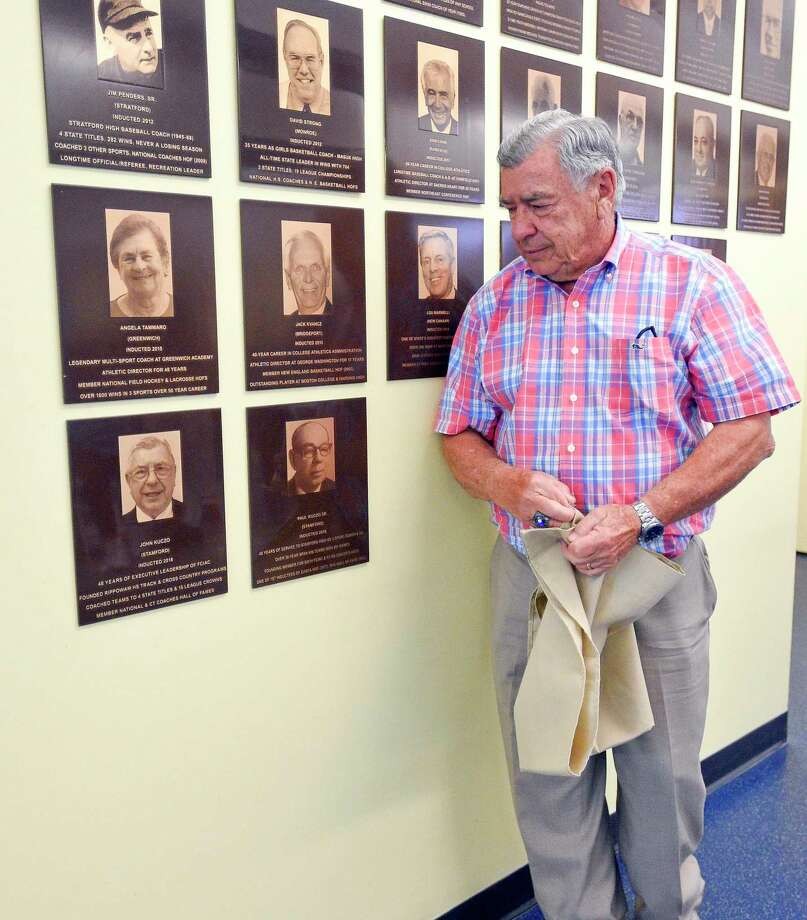 John Kuczo looks down at his plaque, along side the plaque of his father, after unveiling them during a ceremony announcing the 2019 Class of Inductees to Fairfield County Sports Hall of Fame at Chelsea Piers Connecticut in Stamford, Conn. on June 28, 2018. Kuczo and his father were both inducted into the Sports Hall of Fame in 2018. Photo: Matthew Brown / Hearst Connecticut Media / Stamford Advocate