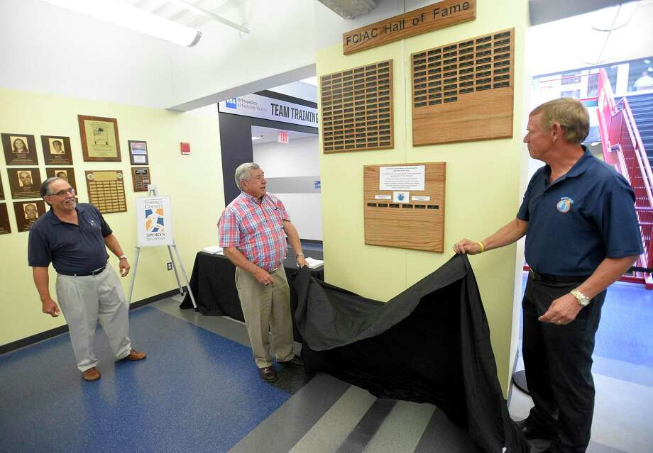 Tom Chiappette, Executive Director of Fairfield County Sports Commission, looks on as John Kuczo and Dave Schulz unveil the new home for the FCIAC Hall of Fame plaques at Chelsea Piers Connecticut in Stamford, Conn. on June 28, 2018. Photo: Matthew Brown / Hearst Connecticut Media / Stamford Advocate