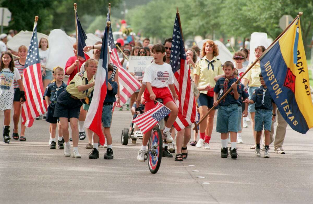 Scout troop 440 leads the Greenwood Forest Civic Association Fourth of July parade HOUCHRON CAPTION (07/05/1998): Boy Scout troop 440 and a unicyclist lead the Greenwood Forest parade.