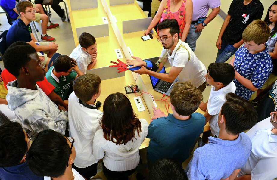 Jesse Costo, who graduated this year, shows how his robotic prostheic arm works to families and fellow students during STEM (science, technology, engineering, and math) Camp at Interdistrict Multi-Magnet High School in Bridgeport, Conn., on Friday June 28, 2019. Photo: Christian Abraham / Hearst Connecticut Media / Connecticut Post