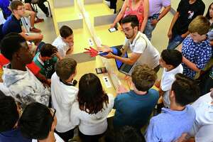 Jesse Costo, who graduated this year, shows how his robotic prostheic arm works to families and fellow students during STEM (science, technology, engineering, and math) Camp at Interdistrict Multi-Magnet High School in Bridgeport, Conn., on Friday June 28, 2019.