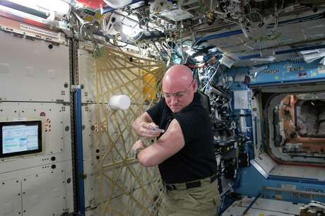 NASA astronaut Scott Kelly gives himself a flu shot for a study on the human immune system.
