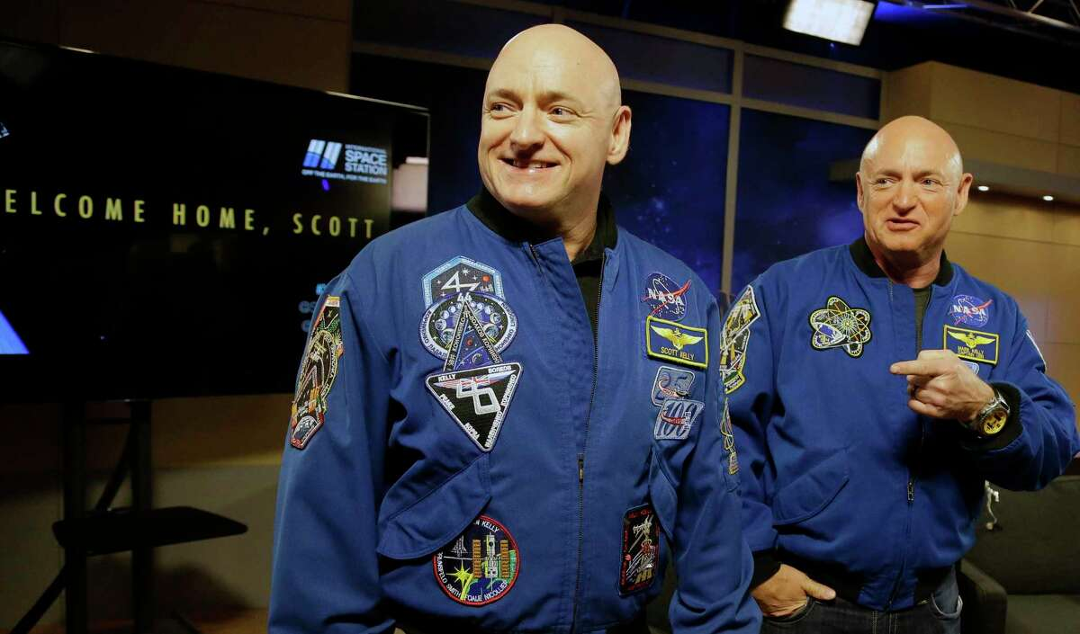 NASA astronaut Scott Kelly, left, and his twin Mark get together before a press conference Friday, March 4, 2016, in Houston. Scott Kelly set a U.S. record with his a 340-day mission to the International Space Station.