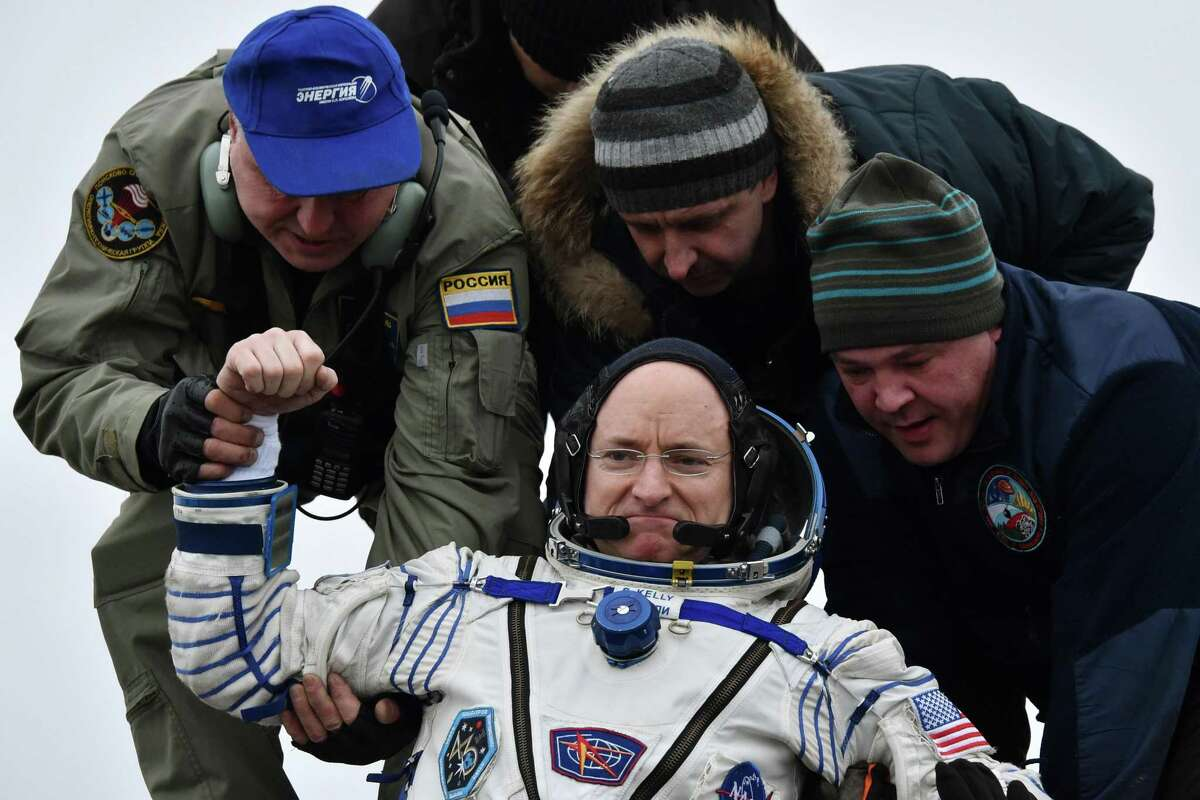 Ground personnel help International Space Station (ISS) crew member Scott Kelly of the U.S. to get off the Soyuz TMA-18M space capsule after landing near the town of Dzhezkazgan, Kazakhstan, Wednesday, March 2, 2016. U.S. astronaut Kelly and Russian cosmonaut Mikhail Kornienko returned to Earth on Wednesday after spending almost a year in space in a ground-breaking experiment foreshadowing a potential manned mission to Mars.