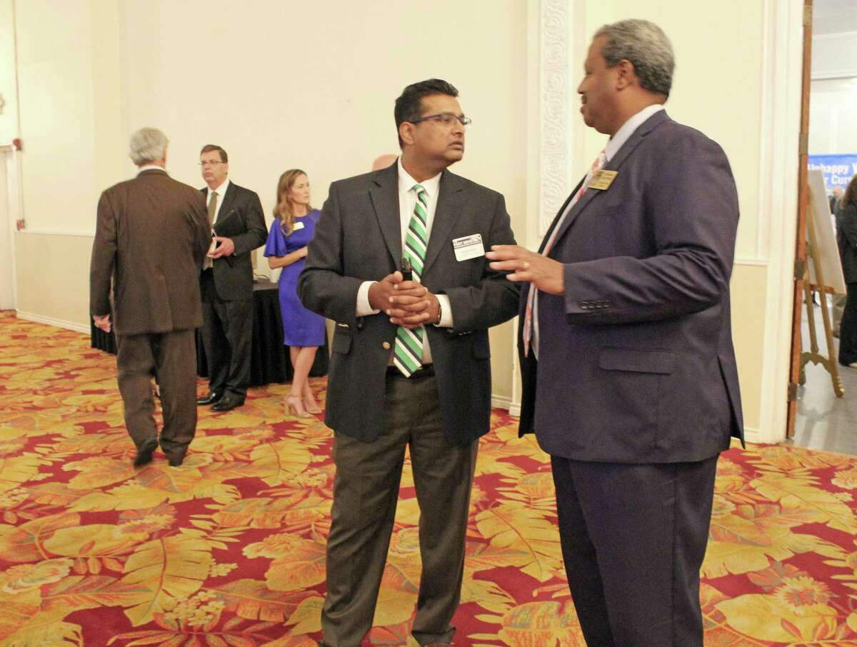 Fort Bend County Commissioner Grady Prestage (right) visits with a guest at the Fort Bend Regional Infrastructure Conference in Richmond on Thursday, June 27.