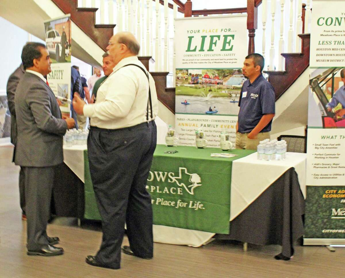 Fort Bend County Judge KP George (left) visit with Meadows Place Mayor Charles Jessup (right) at the Fort Bend Regional Infrastructure Conference in Richmond on Thursday, June 27.