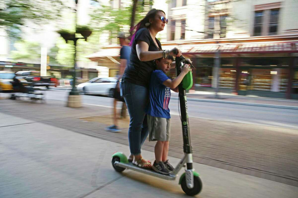 A woman uses a scooter in tandem, which already is prohibited by city ordinance, on the sidewalk along Houston Street downtown last March. Starting Monday, the city will ban riding scooters on all sidewalks and assign three police officers to issue warnings to violators during a 'grace period' in July.