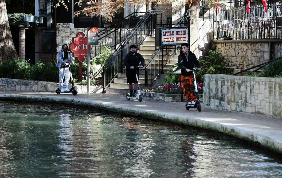 Three scooter riders are seen using the vehicles along the River Walk, which is prohibited by city ordinance, last December near La Villita. Starting Monday, the city will ban riding scooters on all sidewalks and assign three police officers to issue warnings to violators during a 'grace period' in July. (Kin Man Hui/San Antonio Express-News)