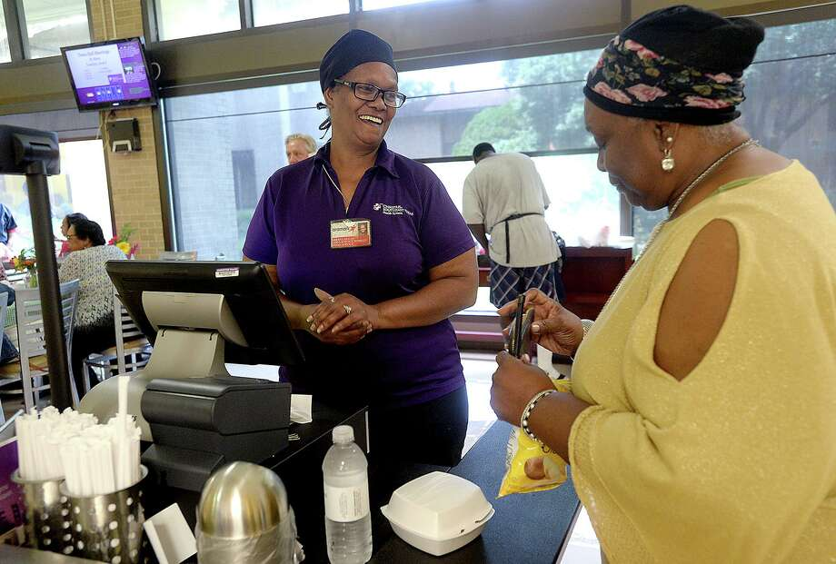 """Sheryl Dugas, a 39-year veteran of the cafeteria, jokes with retired O.B. nurse Nettie Scypion as she pays for her lunch during """"Burger Day"""" at Christus of Southeast Texas St. Mary Hospital in Port Arthur Friday. The lunch offered the hospital cafeteria's famous burgers, a tribute to the staff for their culinary service throughout the years as the hospital nears its closing date next month. Several former hospital employees returned for the event, catching up with one another as they enjoyed the luncheon.  Photo taken Friday, June 28, 2019  Kim Brent/The Enterprise Photo: Kim Brent / The Enterprise / BEN"""