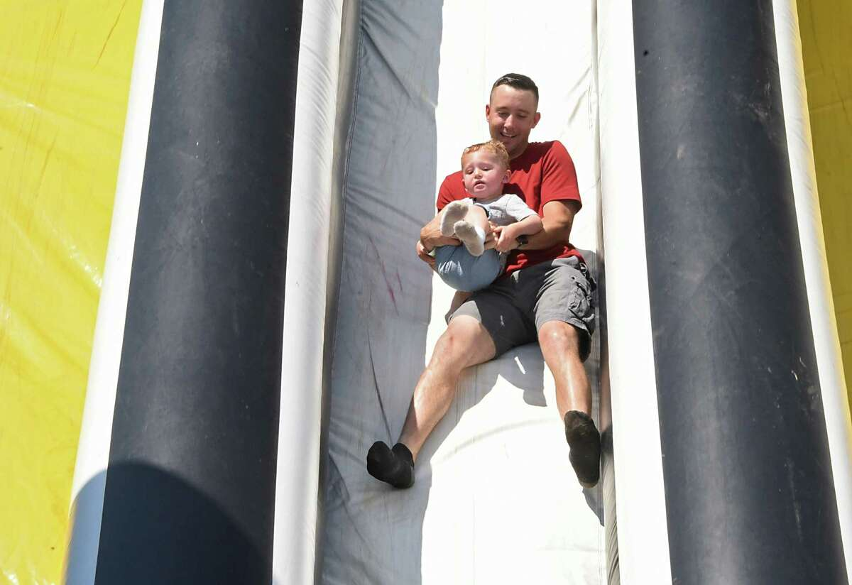 Chris Horwedel of Rotterdam holds his son Calan, 2, as they come down a giant slide as The Big Bounce AmericaOs 2019 tour is held at Ellms Family Farm on Friday, June 28, 2019 in Ballston Spa, N.Y. (Lori Van Buren/Times Union)
