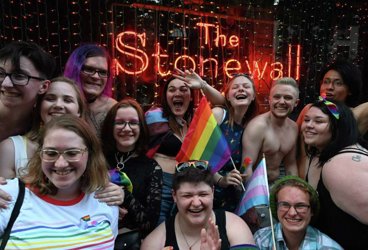 People pose in front of the Stonewall Inn as people gather for the 50th anniversary of the Stonewall Riots in New York, June 28, 2019. - The June 1969 riots, sparked by repeated police raids on the Stonewall Inn -- a well-known gay bar in New York's Greenwich Village -- proved to be a turning point in the LGBTQ community's struggle for civil rights. (Photo by TIMOTHY A. CLARY / AFP)TIMOTHY A. CLARY/AFP/Getty Images