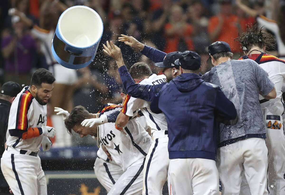Houston Astros third baseman Yuli Gurriel, second from left, celebrates with teammates after hitting a solo homerun during the tenth inning of a major league baseball game at Minute Maid Park on Friday, June 28, 2019, in Houston.