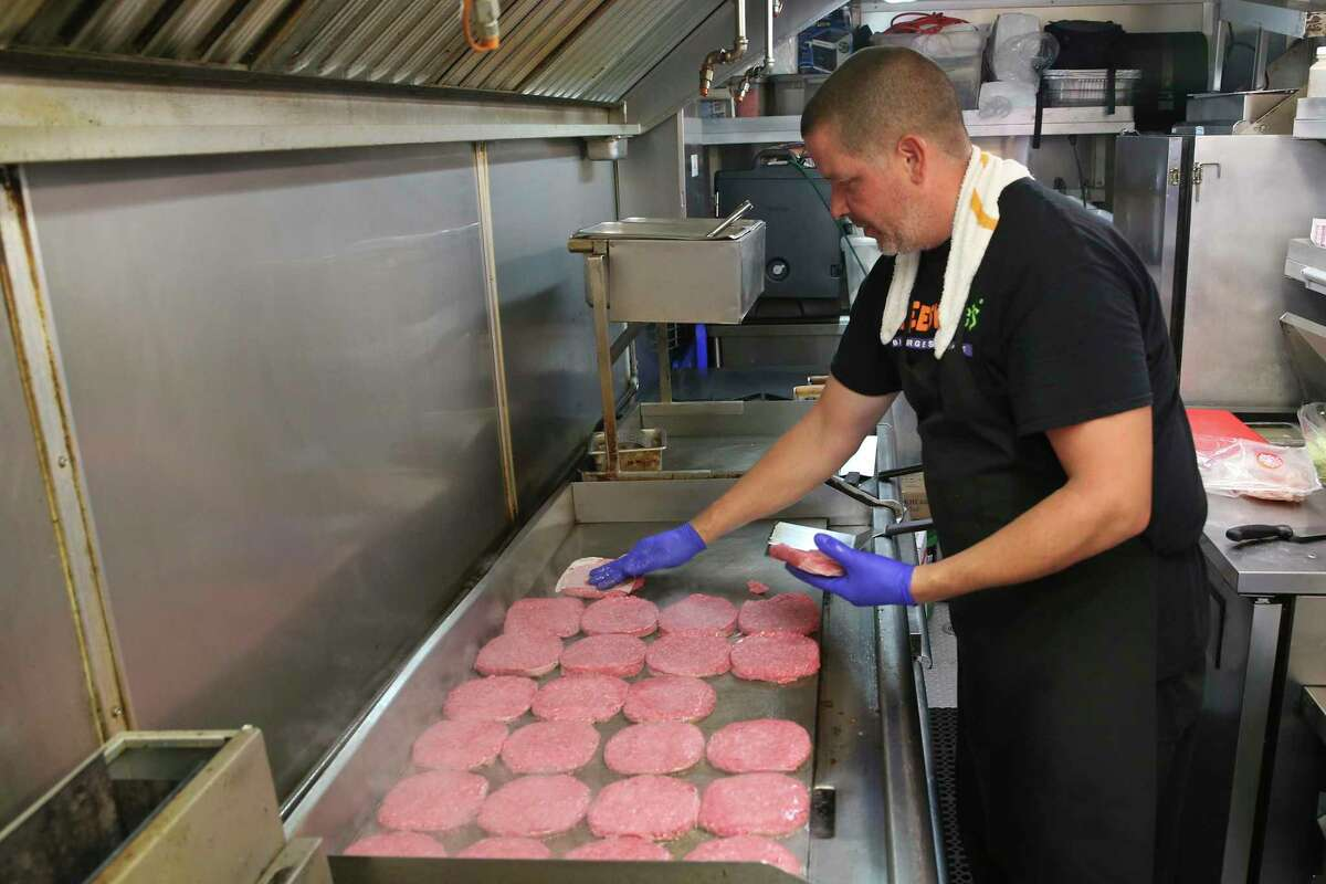 John Chavez cooks beef patties at Cheesy Jane's food truck parked at Main Plaza on June 24, 2019. The food truck is known for its hamburgers.