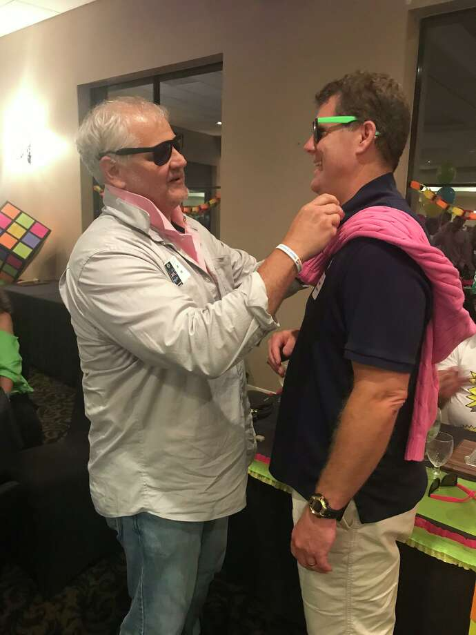 A changing of the guards or pins, Incoming President Scott Perry (l) and Past President Bobby Brennan (r) exchange Presidents pins a the Conroe Noon Lions Club 80's themed Installation Banquet last week. Photo: Courtesy Photo