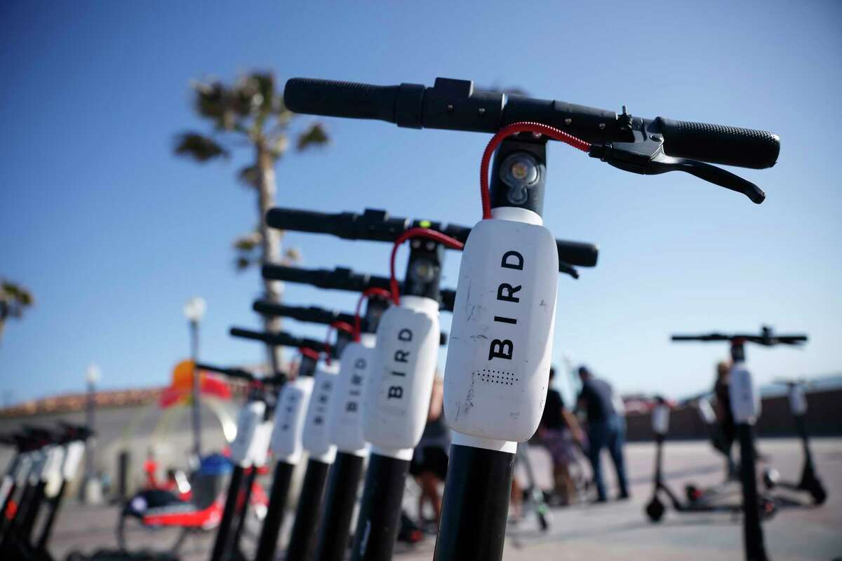 FILE - In this May 28, 2019, file photo Bird scooters are seen along Mission Beach boardwalk in San Diego. The two largest scooter companies in the U.S., Bird and Lime, generally place the responsibility for accidents on riders by listing in their rental agreements that riders relieve the companies of liability. Customers must agree to those terms to ride. Bird says riders are fully insured for anything that might happen as a result of a faulty Bird scooter. (AP Photo/Gregory Bull, File)