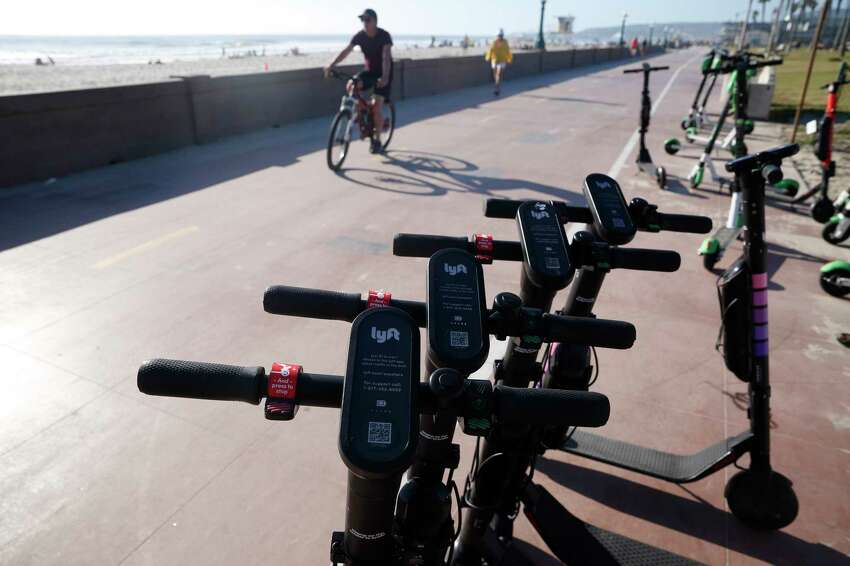 FILE - In this May 28, 2019, file photo Lyft scooters are seen along Mission Beach boardwalk in San Diego. As scooter riders push onto the streets of more than 100 cities worldwide, they?re exposing themselves to liability and most likely not insured for damages they may cause. (AP Photo/Gregory Bull, File)