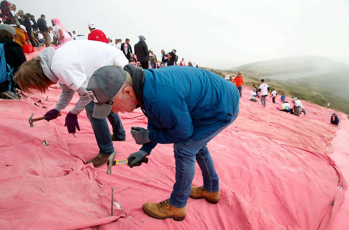 Oleksiy Stepanovskiy (left) and Thomas Songin anchors a section of the giant pink triangle on Twin Peaks to kick off Pride weekend festivities in San Francisco, Calif. on Saturday, June 29, 2019. Stepanovskiy, a Ukranian citizen, timed a business trip to coincide with the installation of the triangle and other Pride fesitivites.