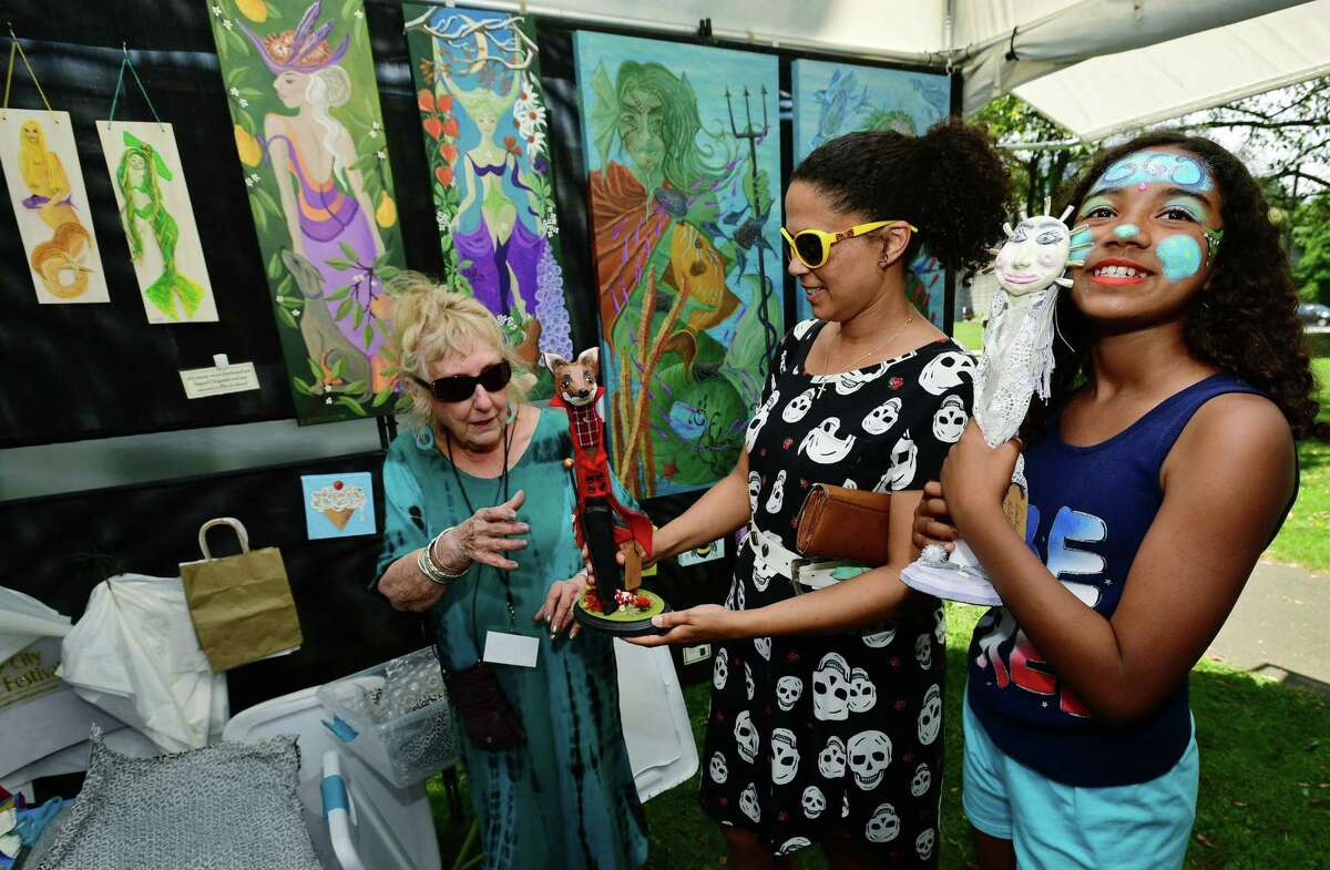 Visitors to Mathews Park including Andrea Johnstone and her daughter Cana Johnstone, 10, buy some art from artist Antoinette Campbell-Hunter during the Norwalk Arts Festival Saturday, June 29, 2019, in Norwalk, Conn.The Norwalk Art Festival features the works of 125 juried artists from local to national talent. They will exhibit a wide variety of media including, photography, drawing, ceramics, jewelry, painting, mixed media, printmaking, fiber, metal sculpture and glass. The festival continues Sunday from 12- 5pm