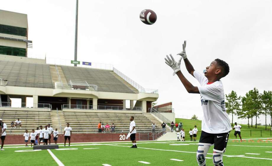 Javion Denney, 12, makes a catch a ball during a drill during Rodney Randle Jr.'s youth football camp at Beaumont ISD Memorial stadium Saturday.