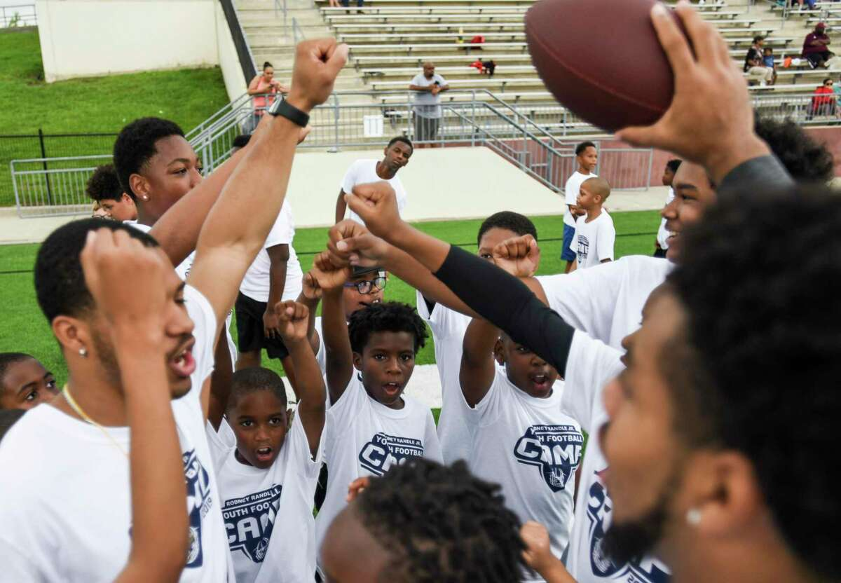 Players and coaches in a huddle during Rodney Randle Jr.'s youth football camp at Beaumont ISD Memorial stadium Saturday. Photo taken on Saturday, 6/29/19. Ryan Welch/The Enterprise