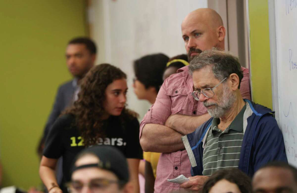 People stood on the side of the walls in a crowded room as the national Sunrise Movement, youth from across Houston held a town hall to raise awareness and support for a Green New Deal Saturday, June 29, 2019, in Houston.
