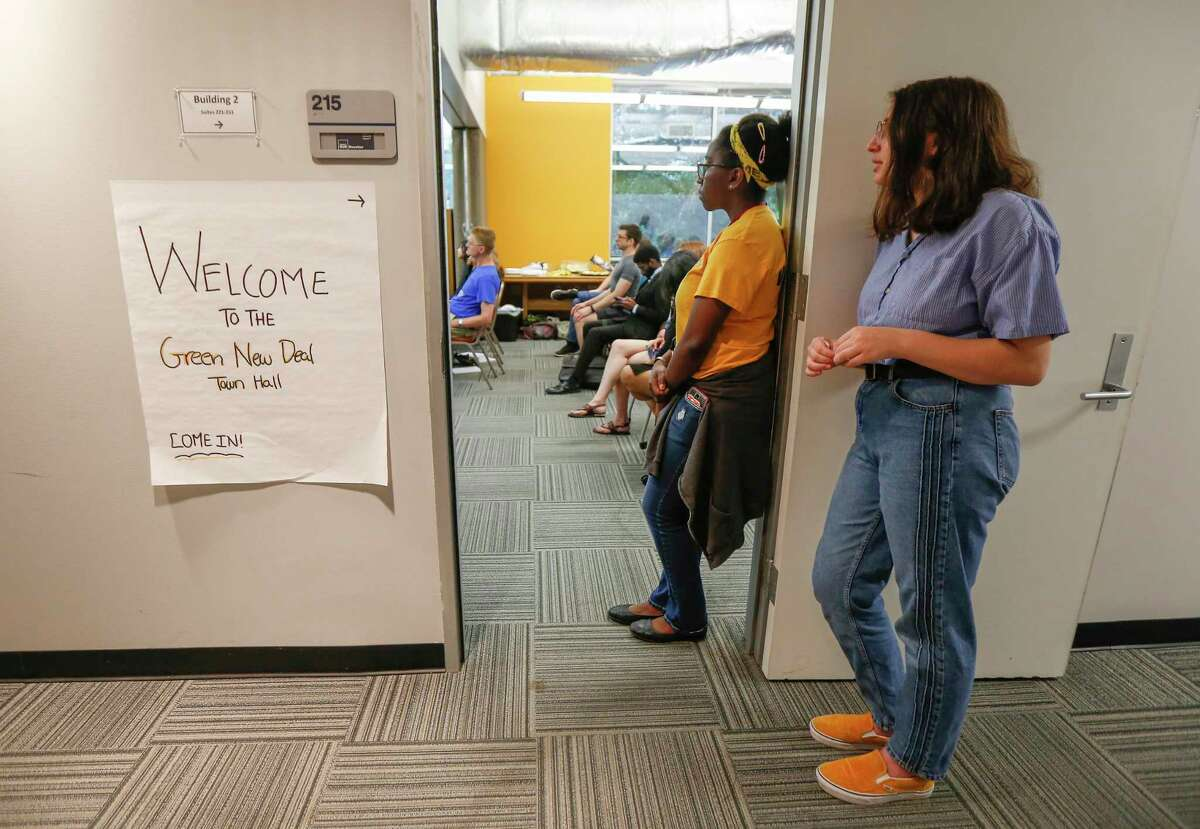People stood outside a crowed room to hear speakers during the national Sunrise Movement, youth from across Houston as they held a town hall to raise awareness and support for a Green New Deal Saturday, June 29, 2019, in Houston.