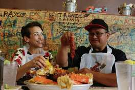 "Autumn Perry-Sevilla and Daniel Sevilla, co-owners and general managers of Smashin Crab, chow down on the ""Perfect Storm,"" which includes shrimp, king crab and mussels, at restaurant's Stone Oak location in San Antonio."