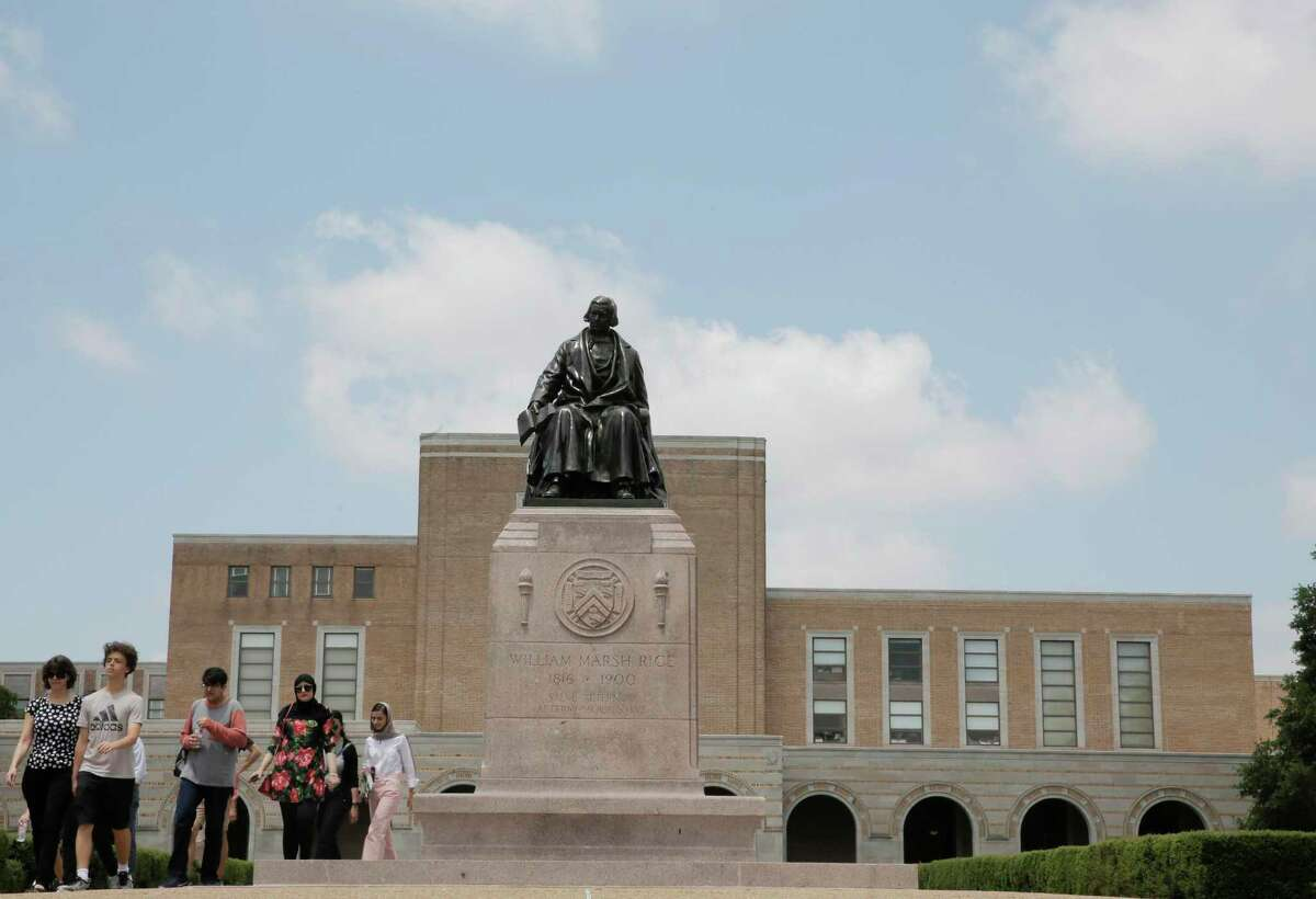 """A tour moves past the statue of Rice University founder William Marsh Rice, who chartered the school with a hefty endowment for """"the white inhabitants"""" of Texas."""