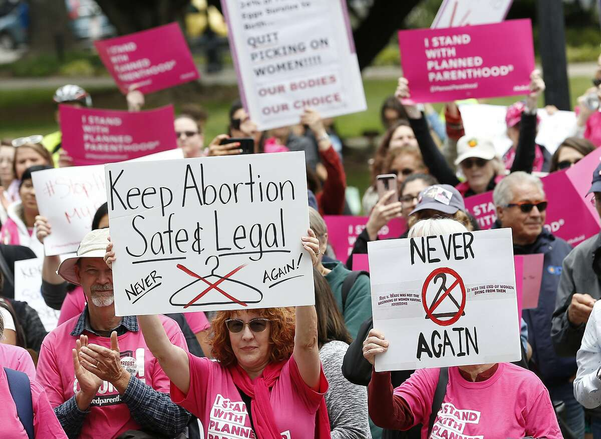 """FILE - In this May 21, 2019, file photo, People gather at the state Capitol to rally in support of abortion rights in Sacramento, Calif. The Trump administration has agreed to postpone implementing a rule allowing medical workers to decline performing abortions or other treatments on moral or religious grounds while the so-called """"conscience"""" rule is challenged in a California court. The rule was supposed to take effect on July 22 but the government and its opponents in a California lawsuit mutually agreed Friday, June 28, 2019 to delay a final ruling on the matter for four months. (AP Photo/Rich Pedroncelli, File)"""