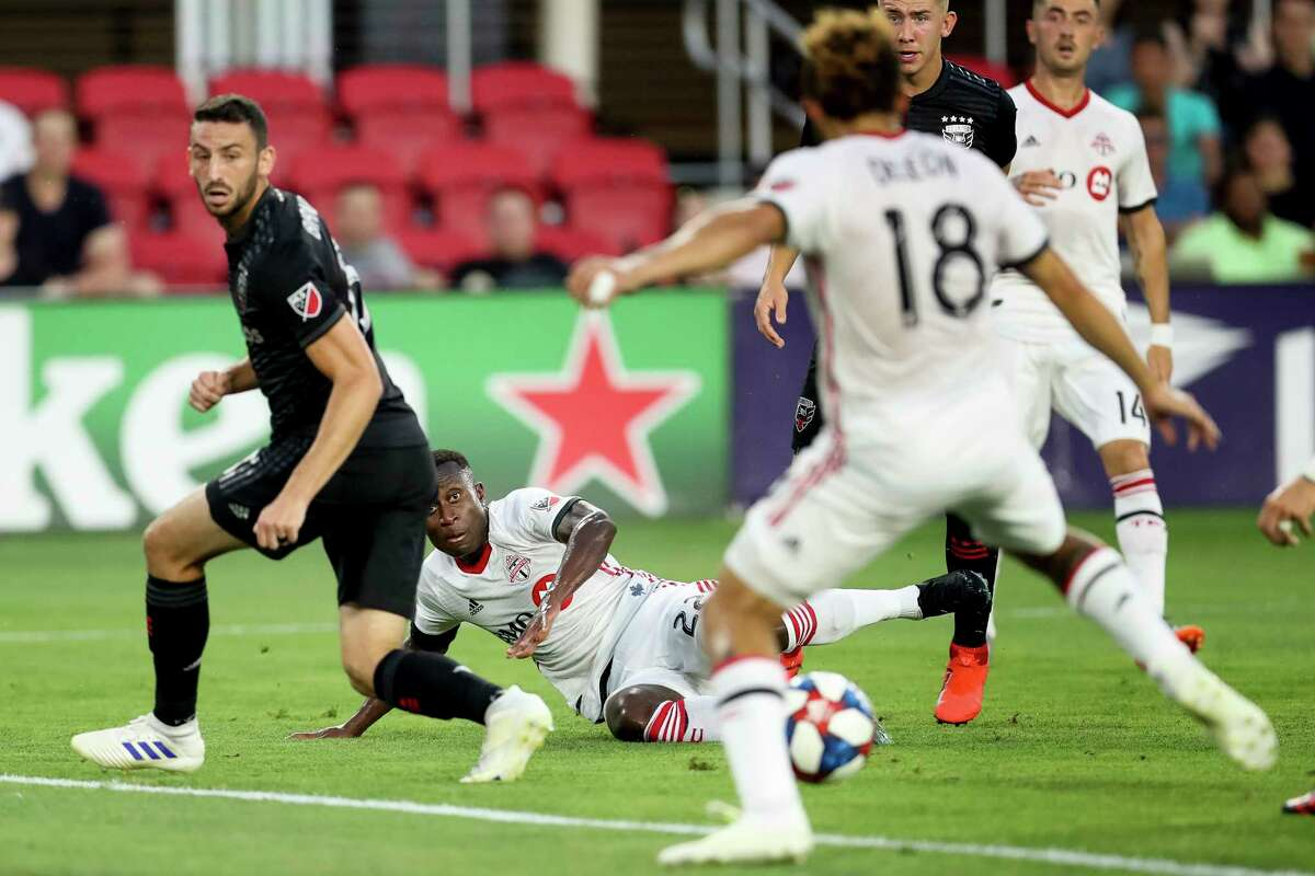 Toronto FC midfielder Richie Laryea (22) watches as Toronto FC midfielder Nick DeLeon (18) scores on his assist during the first half of a soccer match against D.C. United, Saturday, June 29, 2019, in Washington. (AP Photo/Andrew Harnik)