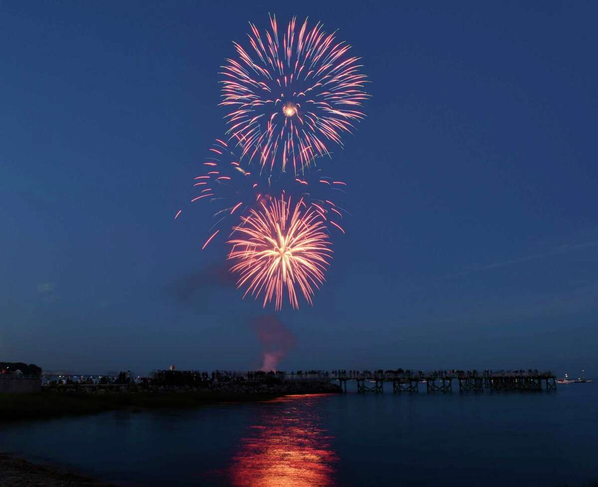 Folks watch fireworks at the Norwalk Independence Day fireworks celebration at Calf Pasture Beach in Norwalk, Conn. Monday, July 3, 2017.