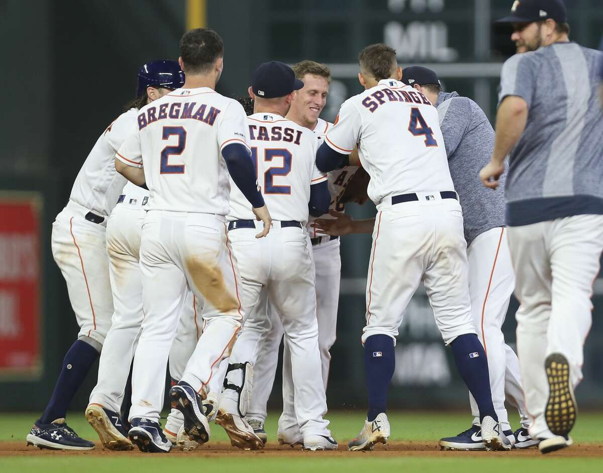 Houston Astros players swarm Houston Astros first baseman Yuli Gurriel (10) as his walk-off double helped the Astros defeat the Seattle Mariners 6-5 during bottom tenth inning of the MLB game at Minute Maid Park on Saturday, June 29, 2019, in Houston. Gurriel had helped the team to win in a walk-off style two nights in a row.