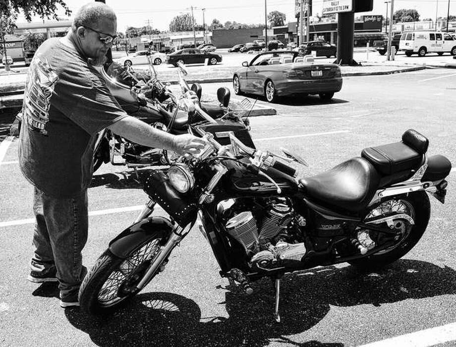 Gregory Prewitt checks his motorcycle after entering it in a bike show at a rally against distracted driving hosted by the Jacksonville Police Department and ABATE. Photo: Marco Cartolano   Journal-Courier