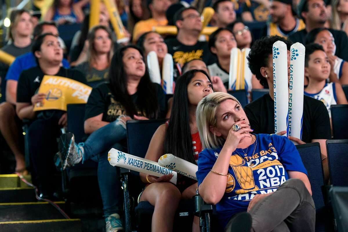Fans watch tentatively after Kevin Durant reinsures his calf, during a watch party for Game 5 of basketball's NBA Finals between the Golden State Warriors and the Toronto Raptors at Oracle Arena in Oakland, Calif., on Monday, June 10, 2019.