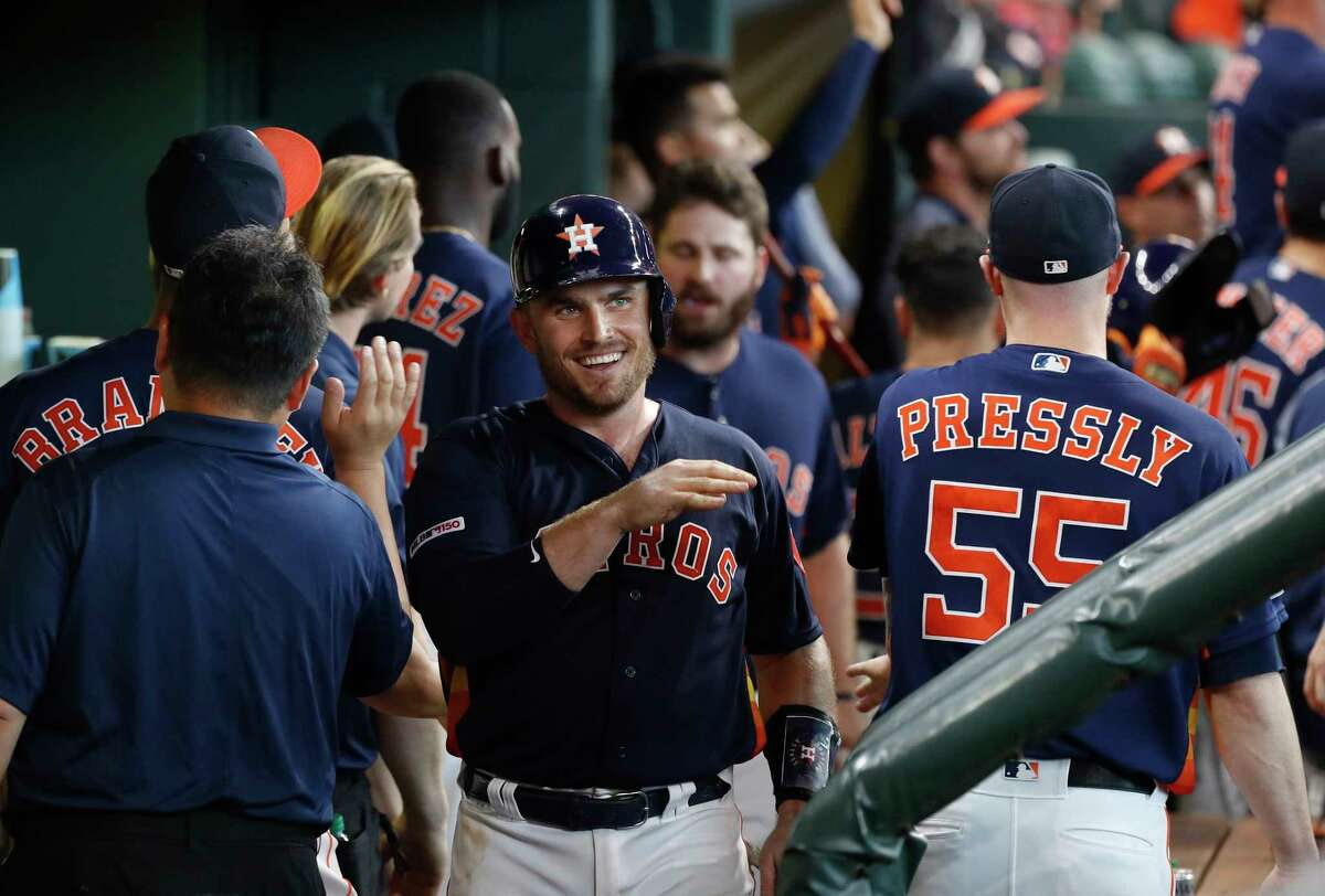 Houston Astros Max Stassi (12) celebrates with teammates after scoring a run on Jake Marisnick's RBI single during the eighth inning of an MLB baseball game at Minute Maid Park,Sunday, June 30, 2019, in Houston.