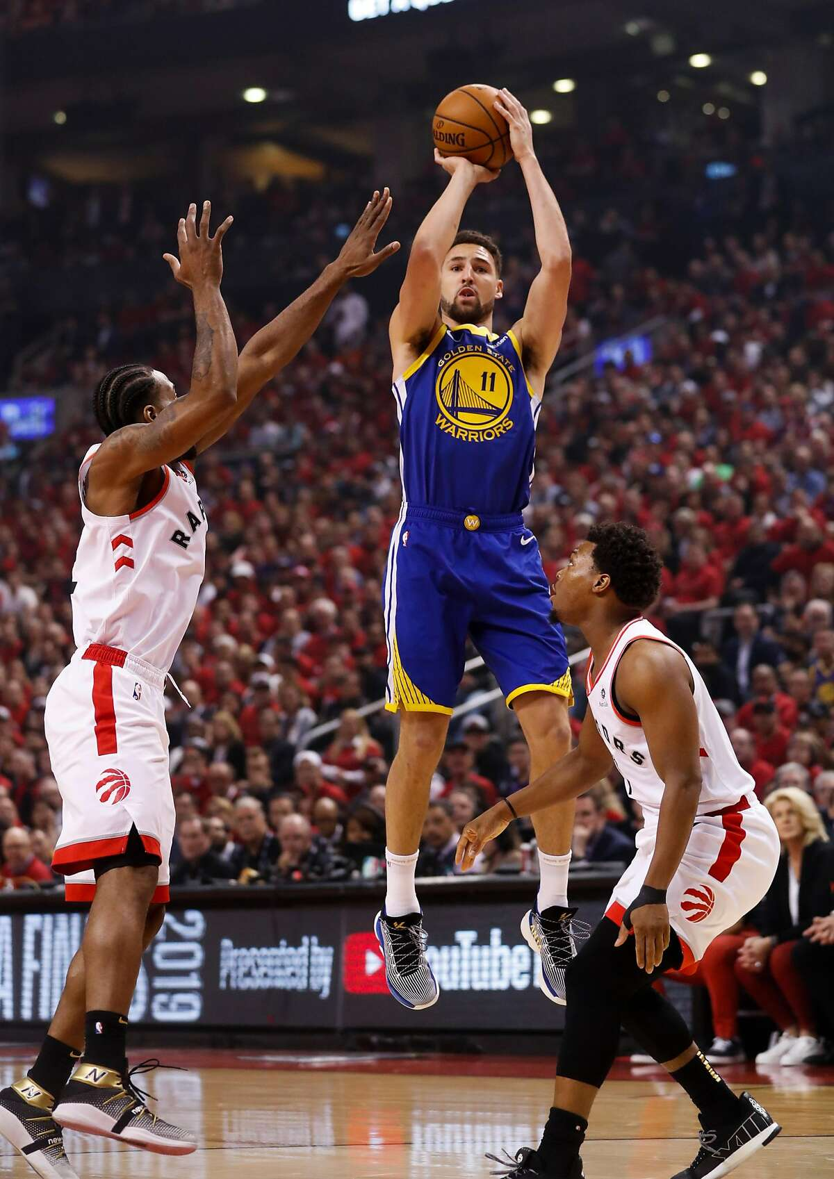 Golden State Warriors' Klay Thompson shoots over Toronto Raptors' Kawhi Leonard and Kyle Lowry in the first quarter during game 2 of the NBA Finals between the Golden State Warriors and the Toronto Raptors at Scotiabank Arena on Sunday, June 2, 2019 in Toronto, Ontario, Canada.