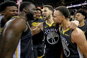 OAKLAND, CALIFORNIA - MAY 16: Stephen Curry #30, Klay Thompson #11 and Draymond Green #23 of the Golden State Warriors celebrate after defeating the Portland Trail Blazers 114-111 in game two of the NBA Western Conference Finals at ORACLE Arena on May 16,