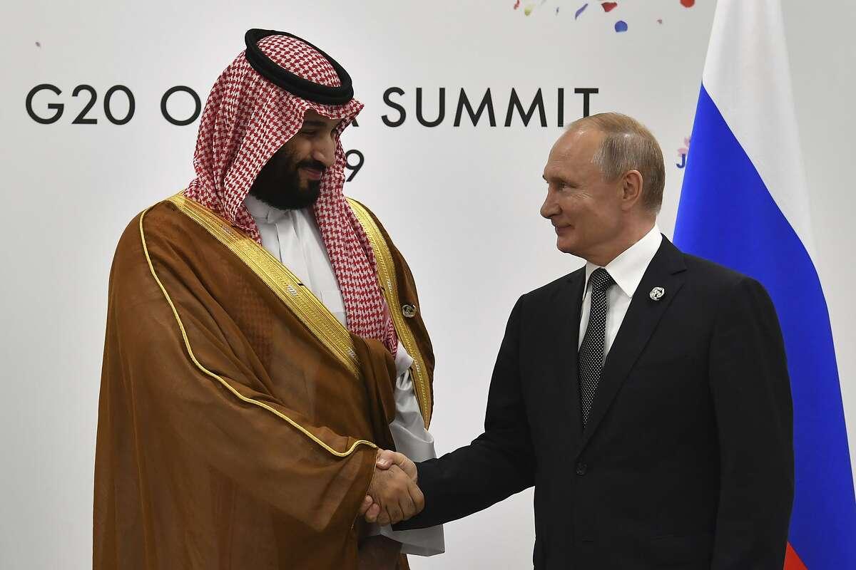 Russia's President Vladimir Putin, right, shakes hands with Saudi Arabia's Crown Prince Mohammed bin Salman during a meeting on the sidelines of the G20 Summit, Saturday, June 29, 2019, in Osaka, Japan. (Yuri Kadobnov/Pool Photo via AP)