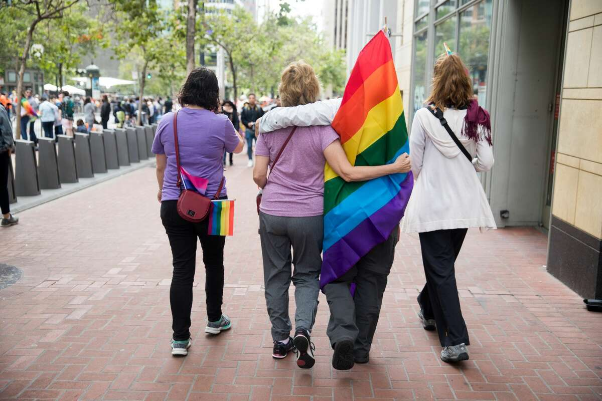 Spectators walk down the sidewalk before the 2019 San Francisco Pride Parade on Market Street in San Francisco on June 30, 2019. This year's celebration was cancelled due to public health risks presented by COVID-19.