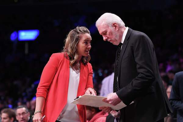 San Antonio Spurs assistant coach Becky Hammon joins head coach Gregg Popovich on the court.