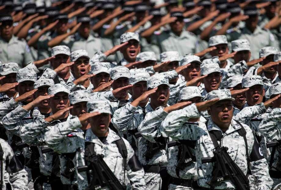 Efectivos de la Guardia Nacional saludan durante la presentación de la nueva fuerza en el Campo Marte de la Ciudad de México, el domingo 30 de junio del 2019. Photo: Christian Palma /Associated Press / Copyright 2019 The Associated Press. All rights reserved.