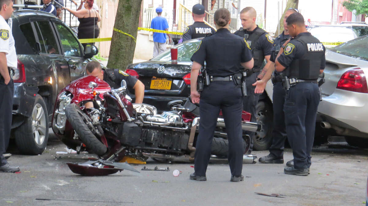 Albany police are searching for a suspect who drove away from a routine traffic stop, crashed into three parked cars and a motorcycle, and then fled the scene on foot, leaving behind two teenagers and two loaded guns in the car on First Street in Albany, N.Y. on June 30, 2019.