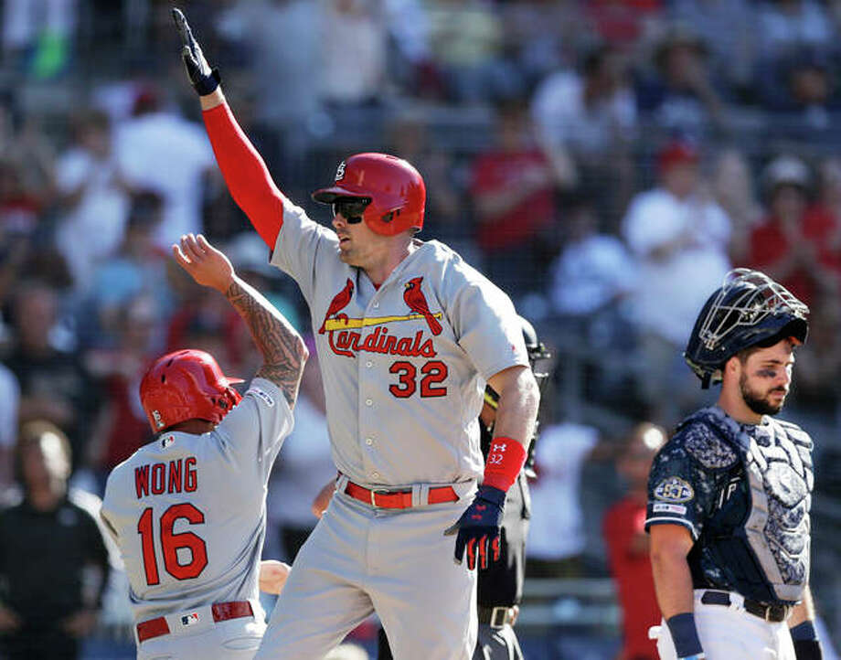 The Cardinals' Matt Wieters (32) celebrates with teammate Kolten Wong (16) after hitting a two-run home run as Padres catcher Austin Hedges looks on during the 11th inning game Sunday in San Diego.