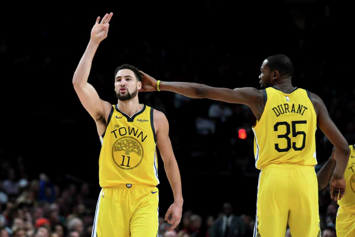 Golden State Warriors guard Klay Thompson, left, is patted on his head by forward Kevin Durant, right, after hitting a shot late in an NBA basketball game against the Portland Trail Blazers in Portland, Ore., Saturday, Dec. 29, 2018. The Warriors won 115-105.