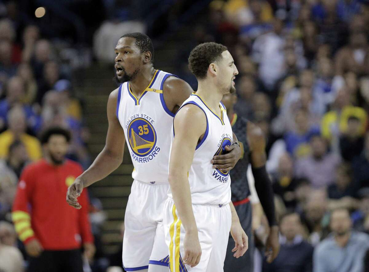 Kevin Durant (35) holds back Klay Thompson (11) who was upset about an offensive foul call against him in the first half as the Golden State Warriors played the Atlanta Hawks at Oracle Arena in Oakland, Calif., on Monday, November 28, 2016.