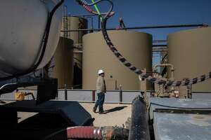 A worker waits as oil is transferred from production tanks to a tanker truck at a Parsley Energy facility near Midland.
