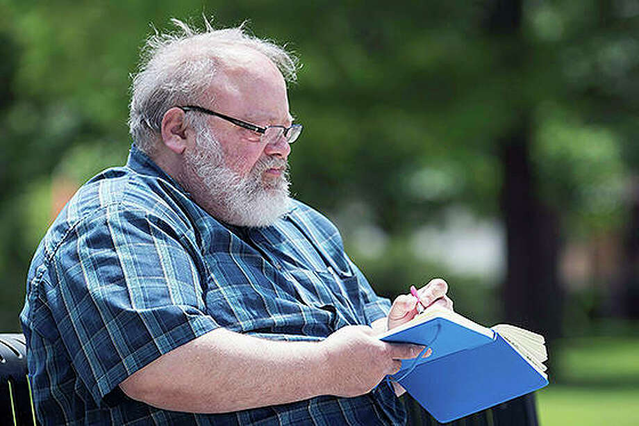 Will Reger writes in his notebook at West Side Park in Champaign. The former Illinois State history professor and Champaign resident was recently introduced as the city of Urbana's first-ever poet laureate. Photo: Stephen Haas | News-Gazette (AP)