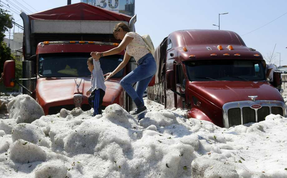 A woman and a child walk on hail in the eastern area of Guadalajara, Jalisco state, Mexico, on June 30, 2019. - The accumulation of hail in the streets of Guadalajara buried vehicles and damaged homes. (Photo by ULISES RUIZ / AFP)        (Photo credit should read ULISES RUIZ/AFP/Getty Images) Photo: ULISES RUIZ/AFP/Getty Images
