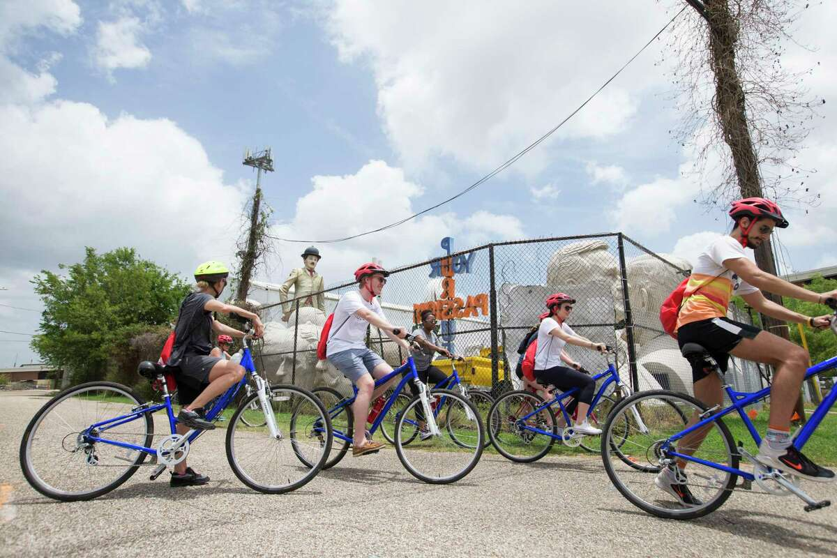 A group of co-workers head to the next stop of the Tour de Brewery's Downtown and Eado Tour after a brief stop at the David Adickes Studio to learn about the history of the famous president head sculptures on Saturday, June 22, 2019, in Houston. The four-hour bicycle tour started from Saint Arnold Brewing Company, to Sigma Brewing Company and 8th Wonder Brewery, then go back to Sant Arnold Brewing Company.