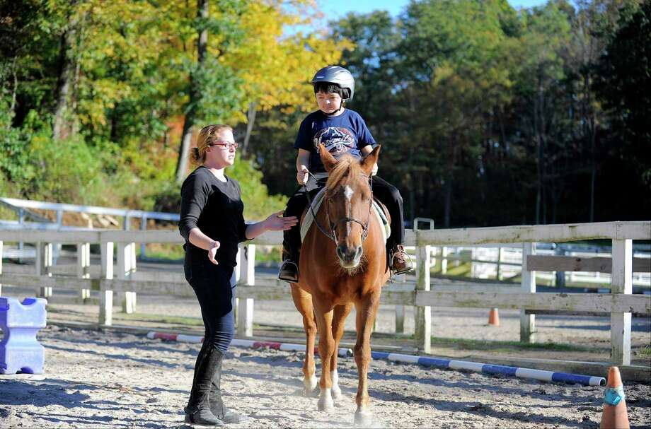 Felicia Benenson, an instructor at Mead Farm, an Equestrian/Boarding facility in North Stamford, Conn., gives a riding lesson Luis Aritake-Wild, 13, of Riverside, Conn. Photo: Matthew Brown / Hearst Connecticut Media / Stamford Advocate